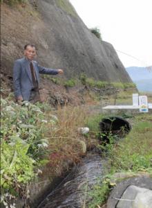 元治水井路土地改良区の小水力発電所は、建設予定地につながる道路の工事が途中でストップしている。左は佐藤高信理事長=11月上旬、由布市庄内町